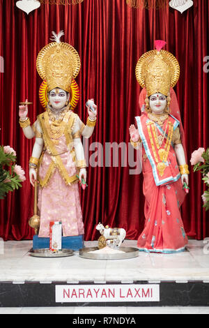 Statues of the deities Narayan and Laxmi at the alter inside the Geeta Temple in Corona, Queens, New York City - Stock Photo