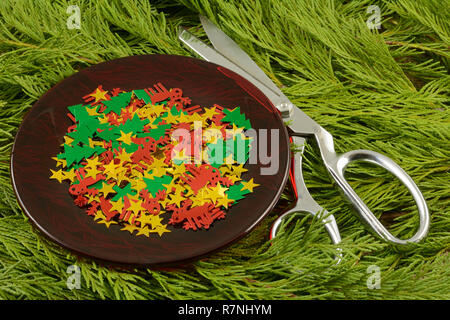 Christmas confetti on red plate with scissors on cedar Christmas greens as supplies for Christmas crafting project - Stock Photo