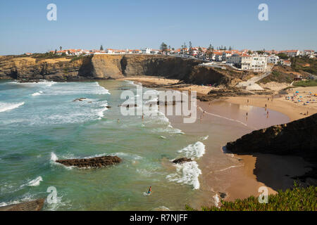 Whitewashed town on cliffs above beach and breaking waves of the Atlantic sea in noon sun, Zambujeira do Mar, Alentejo region, Portugal, Europe