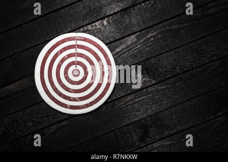 Business achievements concept. Dart on wooden background - Stock Photo
