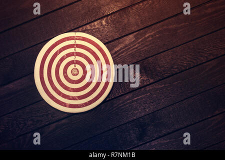 Dart board on dark wooden table. Business concept. - Stock Photo