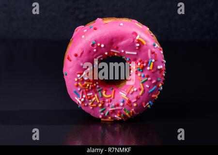 Pink Donut. Frosted sprinkled donut on black background. - Stock Photo