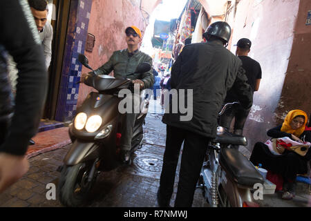 Busy Street scene Marrakech with motorbike and woman begging in the street, Marrakech Medina, Marrakesh, Morocco Africa - Stock Photo