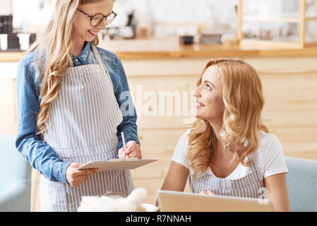 Adorable child taking order from mom in family cafe - Stock Photo