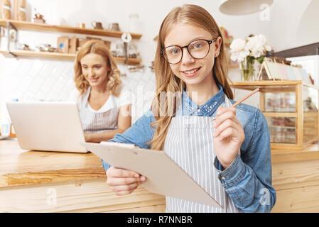 Smart teenage girl taking order in cafe - Stock Photo