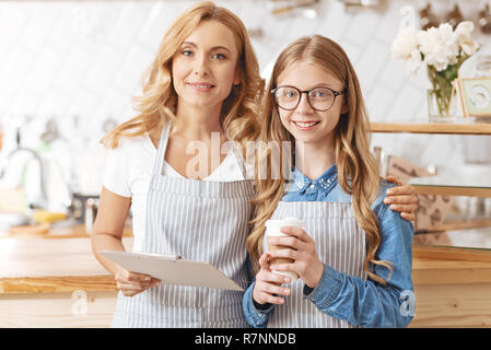 Mother and daughter posing in family cafeteria - Stock Photo