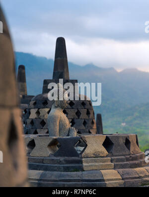 A Buddha stone statue enshrined into a bell shaped stupa looks over the valley on top of buddhist temple of Borobudur, a tourist attraction in Central - Stock Photo