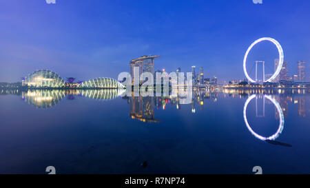 Singapore, 30 Oct 2018: a sunrise skyline view of the Marina Bay with the Garden domes, the Marina Bay Sands hotel and the Flyer Wheel in Singapore. - Stock Photo