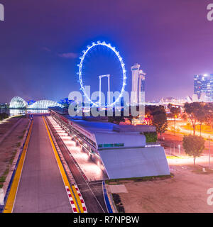 Singapore, 31 Oct 2018: a night viesw of the Formula One Singapore Grand Prix circuit stands in front of the Marina Bay area and the Flyer Wheel. - Stock Photo
