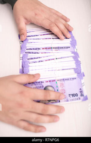 Man is showing 100 rupees new Indian currency on the table. Isolated on the wooden background. - Stock Photo