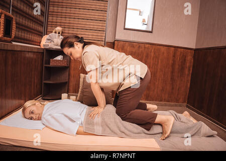 Nice young woman having special Thai massage - Stock Photo