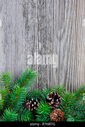 Christmas background: spruce twigs and cones on the old wooden background - Stock Photo