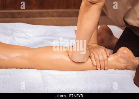 Nice professional skilled masseuse massaging female legs - Stock Photo