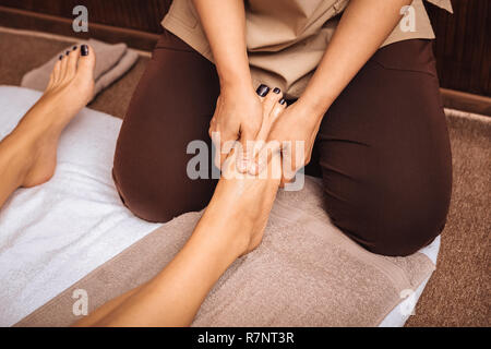 Close up of a female foot being massaged - Stock Photo