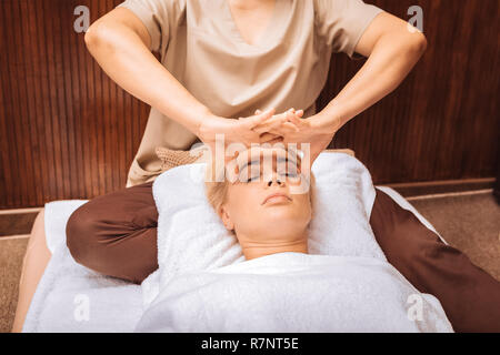 Nice professional female masseuse massaging the temples - Stock Photo