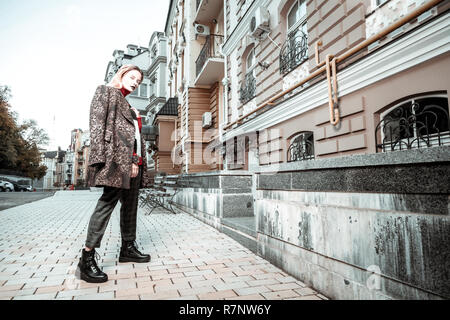 Elegant young woman wearing black boots and grey trousers - Stock Photo