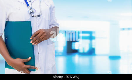 Young beautiful of African-American General Practitioner Doctor in White Coat with stethoscope and folder in Hospital. An Impersonal wide Blue Backgro - Stock Photo