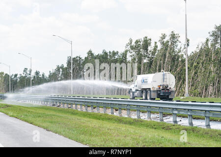 Homestead, USA - April 30, 2018: Truck spraying water watering green grass on highway road in Florida near Miami, tank, trees - Stock Photo