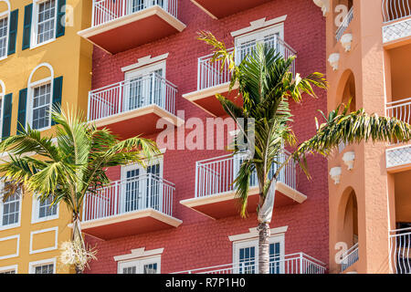 Florida condo, condominium colorful, red multicolored buildings facade exterior with windows, palm trees, real estate property in Spain - Stock Photo