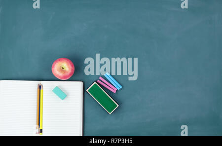 Back to school concept with writing supplies on a green chalkboard - Stock Photo