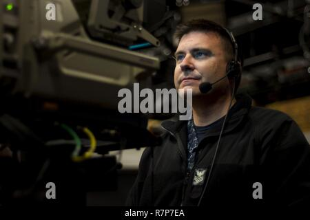 Mass Communication Specialist 1st Class Thomas Miller, camera operator for All Hands Update, monitors broadcasting operations at Defense Media Activity Headquarters. Miller supervises daily operations to inform the Department of Defense and the general public on the latest Navy news daily. - Stock Photo