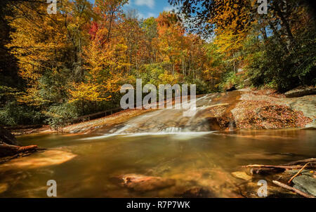 Sliding Rock Falls in the Appalachians of North Carolina in late autumn with fall color foliage and natural swimming pool in the foreground - Stock Photo