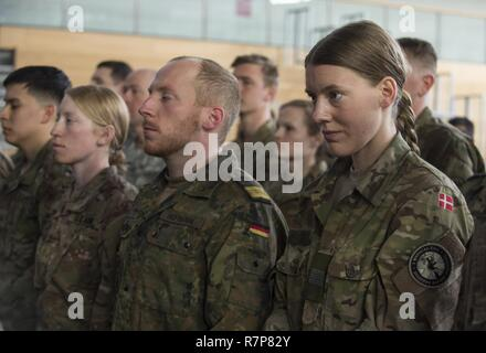 GRAFENWOEHR, Germany – New recipients of the U.S. Army Expert Field Medical Badge (EFMB) stand for the United States of America National Anthem during an EFMB graduation in Grafenwoehr, Germany on March 30, 2017. Approximately 215 candidates from the U.S. Army and ten European partner nations attended this biannual evaluation in hopes of achieving the coveted U.S. Army EFMB but only 64 received it during this year's evaluation. - Stock Photo
