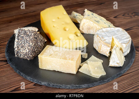 delicious various types of cheese on slate stone background - Stock Photo
