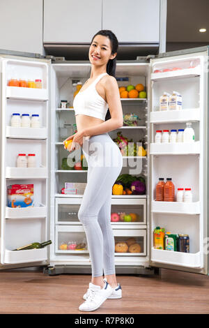 Wearing a sportswear young woman standing in front of the refrigerator - Stock Photo