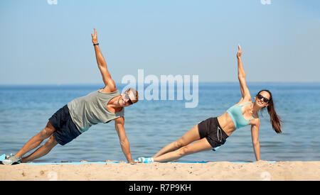 couple doing side plank exercise on summer beach - Stock Photo