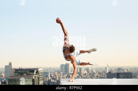 man making parkour jumping over tokyo city - Stock Photo