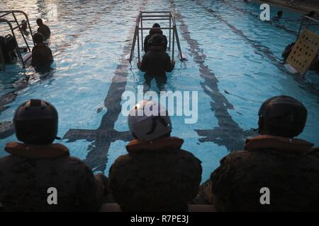 Marines and Sailors assigned to Bravo Company, 1st Battalion, 3rd Marine Regiment, conduct Shallow Water Egress Training at the base pool, aboard Marine Corps Base Hawaii, March 23, 2017. The purpose of this training is to prepare service members for an emergency exit in case of a crash landing over water. - Stock Photo