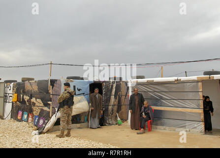 Housh Al Nabi, Lebanon. 10th Dec, 2018. Lebanese army soldiers guard Syrian refugees outside their tent prior the start of the visit of Austrian President Alexander Van der Bellen at a refugee camp in the village of Housh Al-Nabi, which houses more than 700 Syrians coming from Al-Raqqah city. Credit: Marwan Naamani/dpa/Alamy Live News - Stock Photo