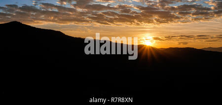 sunrise over mountain silhouette in the Appalachian mountains of western North Carolina in late fall under an expressive blue and cloudy sky - Stock Photo