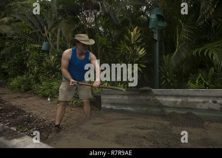 James Parker, manager for Deckchair Cinema, shovels dirt out of a trailer at Deckchair Cinema in Darwin, Australia, Mar 25, 2017. Marines apart of Marine Rotational Force Darwin assisted Parker in setting up the outdoor theater. - Stock Photo