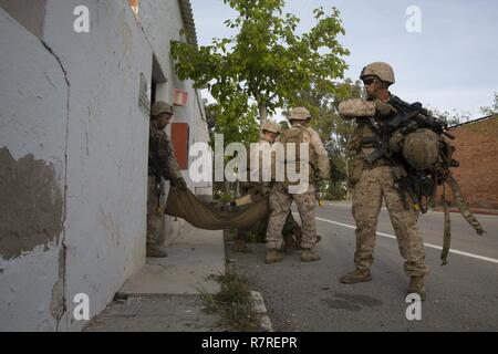 """U.S. Marines and a Navy Corpsman assigned to Special Purpose Marine Air Ground Task Force-Crisis Response-Africa carry a simulated casualty out of a building during a bilateral Military Operation on Urbanized Terrain exercise at Spanish 2nd Special Operations Group """"Granada"""" members in Alicante, Spain, March 30, 2017. The exercise provided an opportunity for Marines and Spanish SOF members to improve interoperability, maintain joint readiness and strengthen relationships. - Stock Photo"""