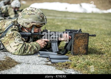 U.S. Army Sgt. 1st Class Jeffrey Mason zeroes his weapon before shooting a weapon qualification during the New York Army National Guard Best Warrior Competition at Camp Smith Training Site March 30, 2017. The Best Warrior competitors represent each of New York's brigades after winning competitions at the company, battalion, and brigade levels. - Stock Photo