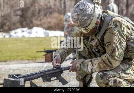 U.S. Army Spc. Richard Blount adjusts his M4's rear sights before shooting a weapon qualification during the New York Army National Guard Best Warrior Competition at Camp Smith Training Site March 30, 2017. The Best Warrior competitors represent each of New York's brigades after winning competitions at the company, battalion, and brigade levels. At the state level they are tested on their physical fitness, military knowledge, endurance, marksmanship, and land navigation skills. The two winners of the competition, one junior enlisted and one NCO, advance to compete at the regional level later t - Stock Photo