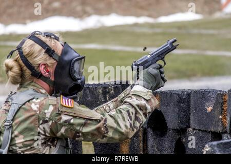 Spec. Courtney Natal fires the M-9 pistol while wearing a protective mask during the stress shoot lane, combining physical tests and shooting events during the New York Army National Guard  Best Warrior Competition at Camp Smith Training Site March 30, 2017. The Best Warrior competitors represent each of New York's brigades after winning competitions at the company, battalion, and brigade levels. At the state level they are tested on their physical fitness, military knowledge, endurance, marksmanship, and land navigation skills. The two winners of the competition, one junior enlisted and one N - Stock Photo