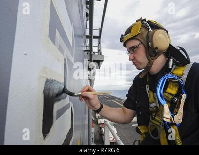 """INDIAN OCEAN (March 30, 2017) Quartermaster 3rd Class Robert Ahrns, from Clare, Mich., paint the outline of a white Battle 'E' on the side of the island superstructure of the amphibious assault ship USS Makin Island (LHD 8). The Battle """"E"""" is awarded annually throughout the Navy to ships whose crews consistently exhibit excellence in wartime capabilities and optimal mission readiness within their platform and region. Makin Island, the flagship for the Makin Island Amphibious Ready Group, with the embarked 11th Marine Expeditionary Unit, is operating in the Indo-Asia-Pacific region to enhance a - Stock Photo"""