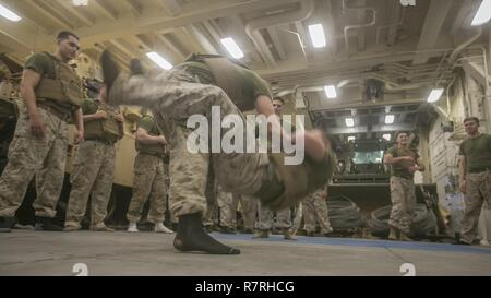 USS SOMERSET, At Sea (March 27, 2017) A U.S. Marine with Light Armored Reconnaissance Company, Battalion Landing Team 1st Bn., 4th Marines, 11th Marine Expeditionary Unit (MEU), executes a counter to the round kick technique during a Marine Corps Martial Arts Program (MCMAP) training session aboard USS Somerset (LPD 25), March 27. MCMAP teaches physical and mental discipline, helping Marines with the 11th MEU maintain a combat-ready body and mindset. The MEU is ready for missions across the range of military operations, such as noncombat evacuations, humanitarian assistance missions, or combat - Stock Photo
