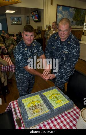 NAVAL STATION GUANTANAMO BAY, Cuba (Mar. 30, 2017) Master Chief Hospital Corpsman Christopher Dingler, (left) and Chief Gunner's Mate Brandon Maye participate in a cake cutting ceremony celebrating the 124th birthday of the Chief Petty Officers at Gold Hill Galley, Naval Station Guantanamo Bay, Cuba. NSGB is on the front lines for regional security in the Caribbean operating area. The base supports U.S. Navy and Coast Guard, and allied nation ships operations by providing contingency and logistical support with superior services and facilities. The base also supports the Department of Homeland - Stock Photo