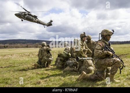 A UH-60 Black Hawk helicopter from A Company, 2-10 Assault Helicopter Battalion, arrives at the pickup zone at Grafenwoehr Training Area, Germany, on April 6. The aviators were taking part in part of a joint-training exercise with Soldiers from 3rd Squadron, 2nd Cavalry Regiment, in anticipation of working together during future Atlantic Resolve missions. - Stock Photo