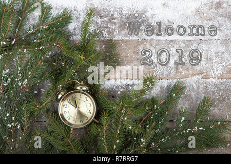 Concept Christmas Eve - text 'Welcome 2019' alarm clock and fir tree branch on a snow-covered wooden background - Stock Photo