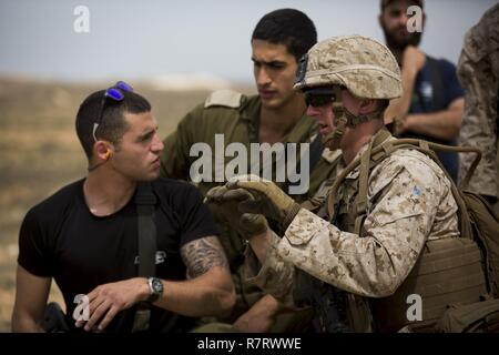 U.S. Marine Lance Cpl. Lucas Cassaubon, a machine gunner with Marine Rotational Force Europe 17.1 (MRF-E), tells an Israeli soldier the fire and manuver plan during a machine gun live-fire in Israel, March 27, 2017. MRF-E works with Israeli forces in developing the interoperability necessary for maintaining Israel's defensive capabilities. - Stock Photo