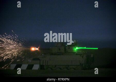 An M2A3 Bradley Fighting Vehicle crew from the 3rd Armored Brigade Combat Team, 1st Cavalry Division shoots at target during the night fire portion of Table VI qualifications at the Udairi Range Complex March 29. The brigade tank and Bradley crews spent about two weeks in the field conducting sustainment gunnery to ensure all the crews qualified at day and night fire to maintain proficiency. - Stock Photo