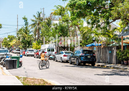 Key West, USA - May 1, 2018: Local woman riding travel bicycle, bike on street road in Florida city on sunny day - Stock Photo