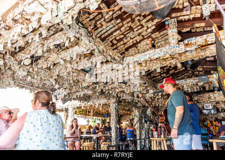 Key West, USA - May 1, 2018: Inside famous Willie T's restaurant bar sign with many dollar bills in Florida, travel, people musicians playing music - Stock Photo
