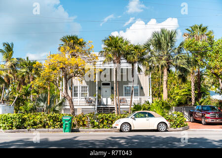 Key West, USA - May 1, 2018: Typical architecture of houses in Florida city island on travel, sunny day, street property real estate, retro car - Stock Photo