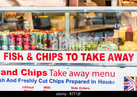 London, UK - September 12, 2018: Greasy street food, fried french fries chips take away menu restaurant sign, soft drinks in SoHo on window display cl - Stock Photo